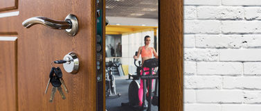 Entrance to gym in fitness club, opened door with woman on elliptical trainer Stock Photos