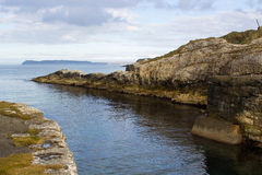 The entrance to the harbor at Ballintoy on the North Coast of Antrim in Ireland stock photography