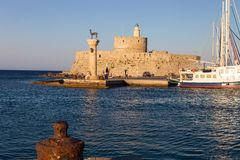 Entrance to the harbor of Rhodes, Greece, behind a pillar and tower Royalty Free Stock Images