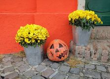 The entrance to the home decorated Halloween pumpkin. The entrance to the home  decorated with pumpkin and yellow chrysanthemums in buckets to Halloween Royalty Free Stock Photography