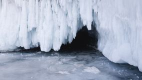 The entrance to the ice cave on a spring day. Travel on the ice of lake Baikal in Siberia. Broken icicles.  stock image
