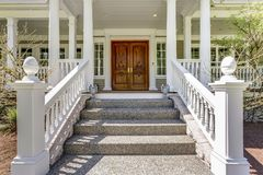 Entrance to a luxury country home with wrap-around deck. Entrance to a luxury country home with covered deck, white columns and staircase stock image