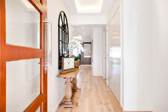 Entrance to a luxury house through the hallway including furnitu. Wooden door entrance to a modern house through the hallway, including traditional watch and Stock Image