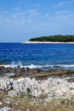 Entrance in to the Mali Losinj bay,Croatia. Pine tree forest and rocky beach in Mali Losinj at the blue adriatic sea Stock Photography