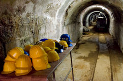 Entrance to a mine. Table with yellow hard hats at entrance to a mine with an arched  tunnel stretching into the distance and a small gauge railway track for Royalty Free Stock Photos
