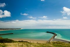 Entrance to Newhaven Harbour Sussex England. A boat heading out to sea from Newhaven harbour Sussex England from Fort Hill with the town of Seaford in the Royalty Free Stock Images