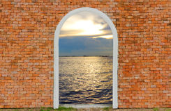 Entrance to ocean of door on wall brick twilight sky Stock Photography