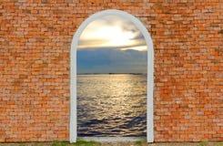 Entrance to ocean of door on wall brick twilight sky Stock Photography