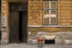 Entrance to old building with small chair. Decaying yellow facade of old building with open gate and small chair with red pillow royalty free stock images