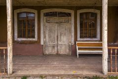 The entrance to the old wooden house, the old sofa is on the veranda. stock photo