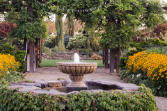Entrance to Paradise. A classic fountain draped with Virginia creeper introduces the entrance to a grand garden beyond on a pathway lined with golden rudbeckias Royalty Free Stock Photos