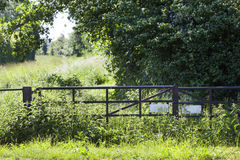 Entrance to a path in the fields. Old metal fence and entrance to a path in the fields Stock Images