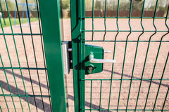 Entrance to the playground of fence and the wicket of the welded. Wire mesh green color with a metal lock and handle royalty free stock image