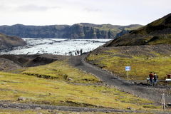 Entrance to the Sólheimajökull Glacier, Iceland. Two hikers confer near the entrance to the Sólheimajökull Glacier in southern Iceland Royalty Free Stock Photos