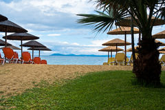 Entrance to sandy beach with stray sunshades and orange chairs. West coast of Sithonia, Greece Royalty Free Stock Photos