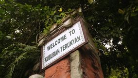 Entrance to Trunyan Cemetery, Bali, sign and human skull on pedestal stock video footage