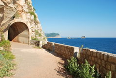 Entrance to the tunnel at the coast of the Adriatic Sea. Montenegro. Entrance to the tunnel to a grief at the coast of the Adriatic Sea. Montenegro Stock Photos