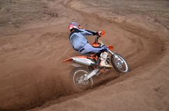 Entrance to turn the sandy track racer of motocross motorcycle w Royalty Free Stock Photos