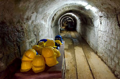 Entrance to underground mine. Table with yellow hard hats at entrance to a mine with an arched tunnel stretching into the distance and a small gauge railway Stock Photo