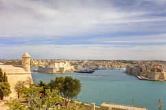Entrance to the Valletta city harbor at Malta, with many historic buildings along the coastline.  Royalty Free Stock Image