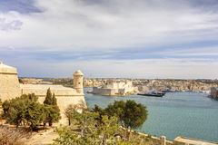 Entrance to the Valletta city harbor at Malta, with many historic buildings along the coastline.  Stock Photos
