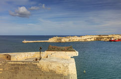 Entrance to the Valletta city harbor at Malta, with many historic buildings along the coastline and a lighthouse.  Royalty Free Stock Image