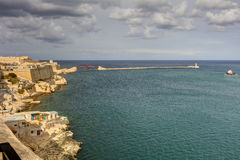 Entrance to the Valletta city harbor at Malta, with many historic buildings along the coastline and a lighthouse.  Stock Photo