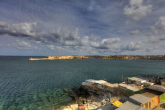 Entrance to the Valletta city harbor at Malta, with many historic buildings along the coastline and a lighthouse.  Royalty Free Stock Photo