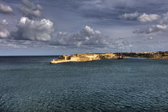 Entrance to the Valletta city harbor at Malta, with many historic buildings along the coastline and a lighthouse.  Royalty Free Stock Photography