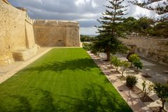 Entrance to the walled city of Mdina in Malta. A beautiful high stone wall, that envelopes the city of Mdina on the island of Malta. Fronted by an immaculate royalty free stock photos