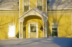 Entrance to yellow home at sunrise in winter,  Lyndonville, VT Royalty Free Stock Images