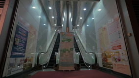 Entrance with up and down escalators. HONG KONG - NOVEMBER 09, 2015: Shopping mall entrance with up and down escalators and advertising banners stock footage