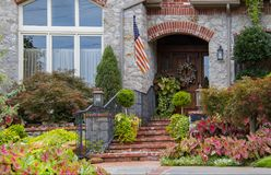 Entrance and window to beautiful rock upscale house with lush landscaping and American flag and wreath on door royalty free stock photos