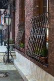 Entrance, windows and antique metal street light. Flowers Stock Photos