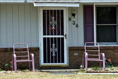 Entranceway. An entrance with maroon door, shutters, and pink chairs Stock Photography