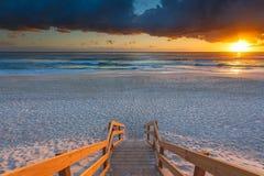Entrata australiana della spiaggia con le scale in priorità alta ad alba Fotografia Stock