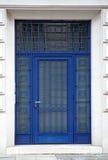 Entrata blu della porta del ferro con le pareti bianche fotografie stock