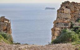 Entrata con dell'entrata nessun'e privata di Eingang iscrizione Verboten sulle scogliere di Dingli con l'isola maltese Filfla in immagini stock