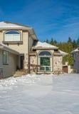 Entrata della casa di lusso con l'iarda anteriore in neve Fotografie Stock Libere da Diritti