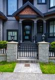 Entrata della casa residenziale con il portone di griglia del metallo nella parte anteriore Casa colorata buio con il portone del fotografie stock
