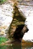 Entrata della caverna con il flusso Fotografia Stock Libera da Diritti