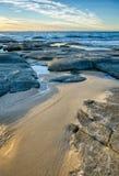 Entrata della spiaggia rocciosa di vista sul mare con la sabbia, le grandi rocce ed i massi in acqua di mare calmo fotografia stock