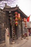 Entrata elaborata ad una casa cinese antica con le sculture, le lanterne rosse, le scritture in oro e una bandiera rossa Pechino, immagine stock