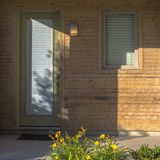 Entrata principale bianca con la lastra di vetro di vetro di una casa di legno fotografie stock