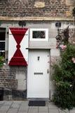 Entrata principale con gli otturatori rossi & bianchi su una casa medievale Fotografie Stock Libere da Diritti