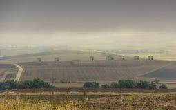 Entre Apulia e Basilicata: paisagem montanhosa com as casas da quinta na terra arada dominada por nuvens, Itália imagens de stock
