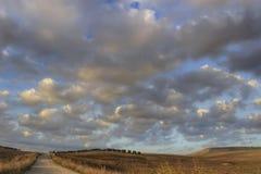 Entre Apulia e Basilicata: a paisagem montanhosa com o bosque verde-oliva na terra arada dominou por nuvens, Itália Estrada secun foto de stock