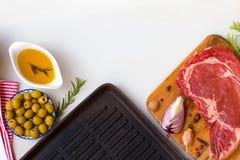 Entrecôte crue fraîche de boeuf avec des ingrédients à faire cuire le dîner et la poêle taesty, vue supérieure avec l'espace pour images stock
