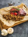 Entrecostos de porco assadas, trigo mourisco com cogumelo e tomates na placa de corte de madeira Imagens de Stock Royalty Free