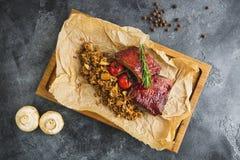Entrecostos de porco assadas, trigo mourisco com cogumelo e tomates na placa de corte de madeira do vintage velho Configuração li Imagem de Stock Royalty Free